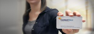 professional woman holding business card with ContextWest information
